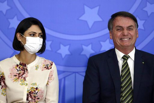 Brazil's President Jair Bolsonaro smiles sitting next to his wife Michelle Bolsonaro wearing a protective face mask, during the swearing ceremony of his new justice minister, at the Planalto presidential palace, in Brasilia, Brazil, Wednesday, April 29, 2020.