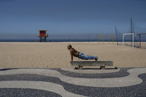 A man exercises on a bench amid the new coronavirus pandemic on Copacabana beach, Rio de Janeiro, Brazil, Wednesday, April 29, 2020. Rejection of quarantine to help contain the spread of COVID-19 is evident among the people soaking up sunshine in the beachside neighborhoods of Copacabana and Barra da Tijuca.