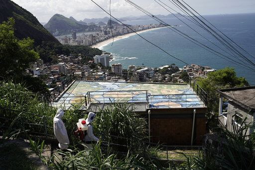 Water utility workers from CEDAE disinfect in the Vidigal favela, which overlooks the oceanfront Leblon and Ipanema neighborhoods, in an effort to curb the spread of the new coronavirus, in Rio de Janeiro, Brazil, Friday, April 24, 2020.