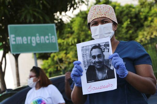 "A health worker holds a photo of a person he said was his colleague who died of COVID-19, at a protest outside ""Pronto Socorro 28 de Agosto"" Hospital in Manaus, Brazil, Monday, April 27, 2020. Cases of the new coronavirus are overwhelming hospitals, morgues and cemeteries across Brazil as Latin America's largest nation veers closer to becoming one of the world's pandemic hot spots."