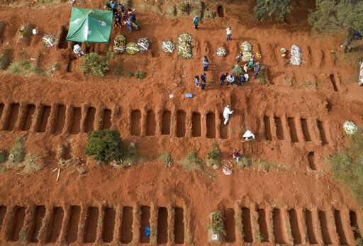 Cemetery workers in protective clothing bury a person who died of COVID-19, at the Vila Formosa cemetery in Sao Paulo, Brazil, Thursday, April 30, 2020.