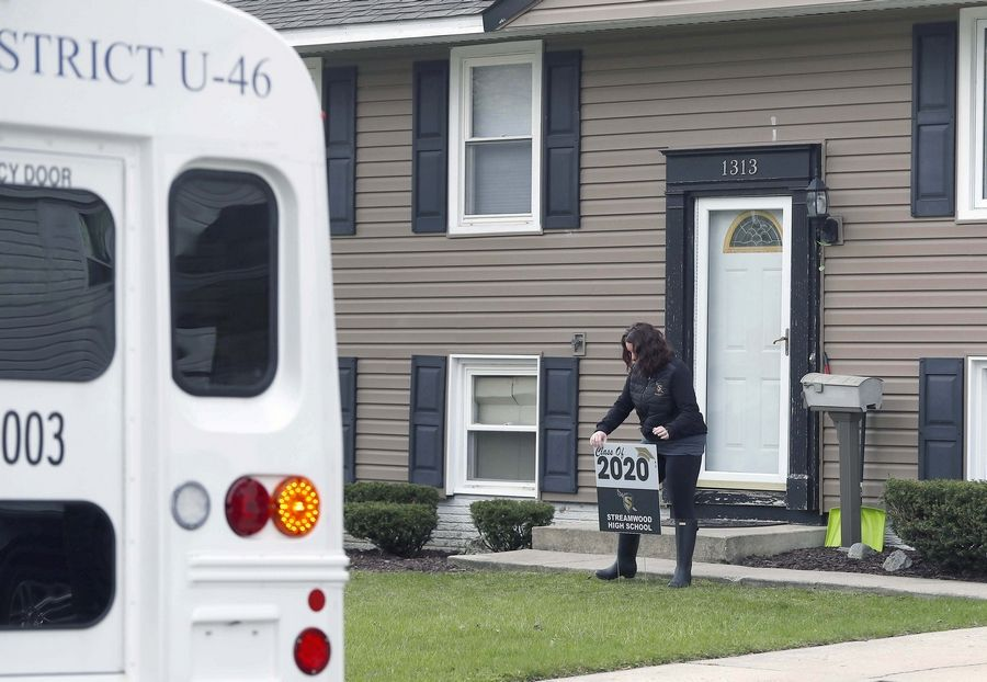 Streamwood High School Principal Jennifer Van Deusen and 80 volunteers deliver yard signs to the homes of graduating seniors. Schools across the suburbs are recognizing their soon-to-be graduates in a variety of ways in the absence of having graduation ceremonies.