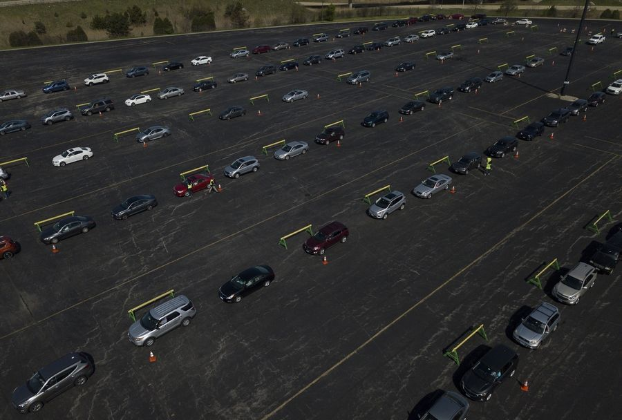 Hundreds of cars filled the parking lot across from Boomers Stadium in Schaumburg waiting in line for some of the 70,000 free masks the village is giving away this week.