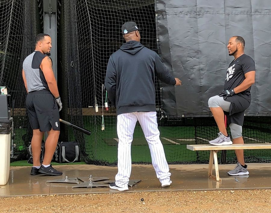 White Sox first baseman Jose Abreu, left, and designated hitter Edwin Encarnacion visit with first-base coach Daryl Boston, middle, during spring training in February at Camelback Ranch.