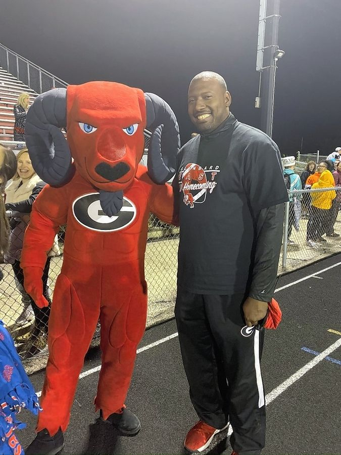 Glenbard East athletic director Dwayne Bates, right, with the school mascot.