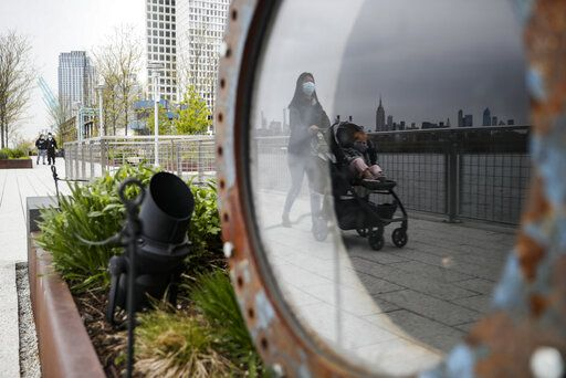 "A visitor pushes a stroller while wearing a protective mask at Domino Park, Friday, May 8, 2020, in the Brooklyn borough of New York. Some parks will see stepped-up policing to stem the spread of the coronavirus, New York City Mayor Bill de Blasio said Friday. He also announced that 2,500 members of a ""test and trace corps"" will be in place by early June to combat the virus."