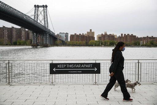 "A dog walker passes a social distancing sign while wearing a protective mask at Domino Park, Friday, May 8, 2020, in the Brooklyn borough of New York. Some parks will see stepped-up policing to stem the spread of the coronavirus, New York City Mayor Bill de Blasio said Friday. He also announced that 2,500 members of a ""test and trace corps"" will be in place by early June to combat the virus."