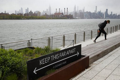 "A visitor wearing a protective mask walks through Domino Park, Friday, May 8, 2020, in the Brooklyn borough of New York. Some parks will see stepped-up policing to stem the spread of the coronavirus, New York City Mayor Bill de Blasio said Friday. He also announced that 2,500 members of a ""test and trace corps"" will be in place by early June to combat the virus."
