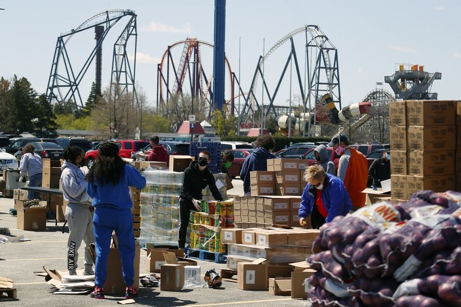 Volunteers sort and prepare food for clients. A collaboration between the Six Flags Great America theme park, the village of Gurnee and the Northern Illinois Food Bank gave away free food to 3,000 families in the theme park parking lot in Gurnee Saturday.