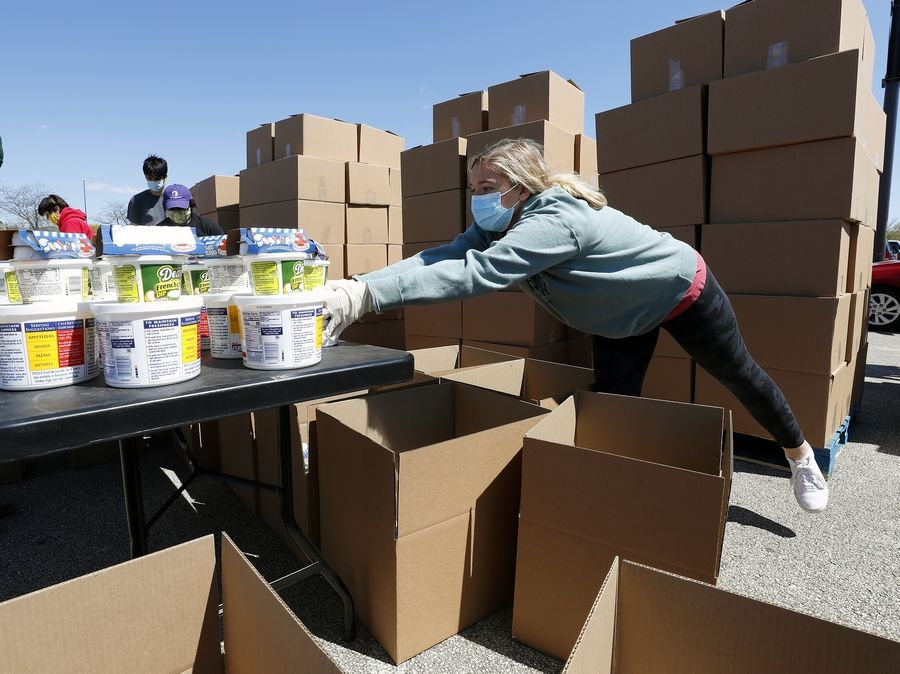 Brenna Davidson of Wheaton reaches to grab more food during packing for a collaboration between the Six Flags Great America theme park, the village of Gurnee and the Northern Illinois Food Bank to give away free food for 3,000 families in the theme park parking lot in Gurnee Saturday.