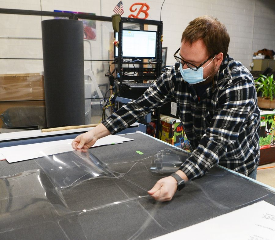 Robert Ferris removes plastic pieces cut from a sheet at Frankenstitch, a veteran-owned printing company in Wheeling that is now making and selling face shields and masks. He plans to donate a portion of proceeds to fellow veterans.