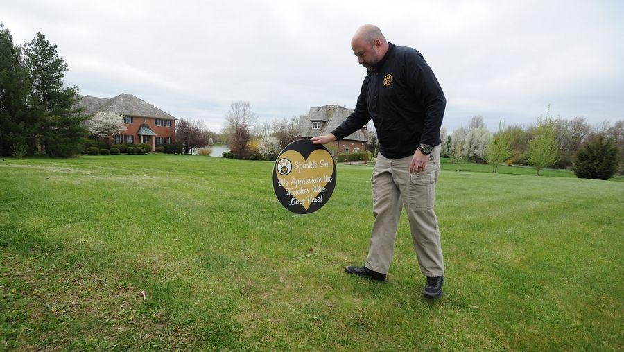 Principal Kurt Preble, of West Oak Intermediate School in Diamond Lake School District 76 plants a sign at the home of one of the teachers, just one of 15 stops he will make as part of appreciation week for the teachers.