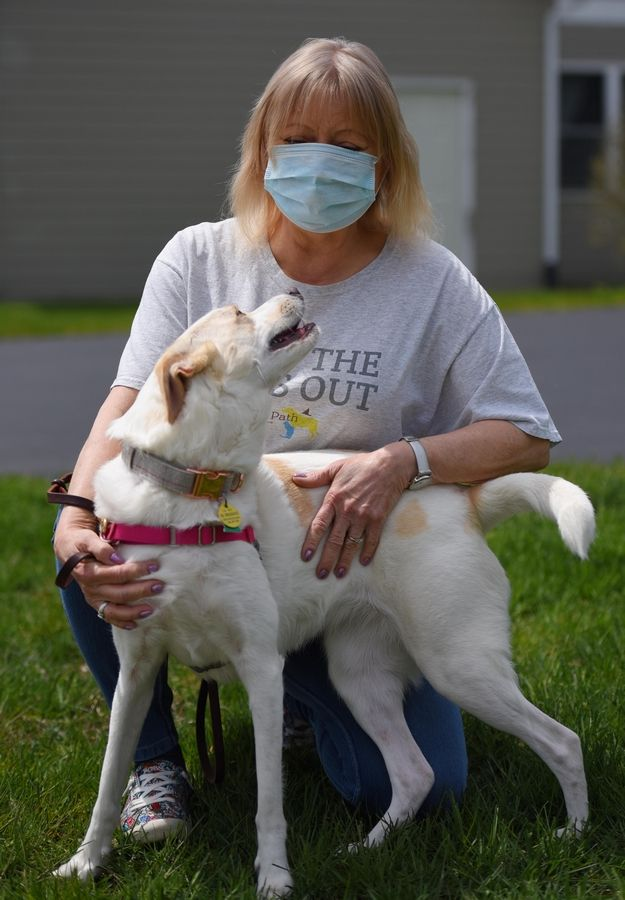 Marsha Thomas poses with a client's dog. She is a branch manager for Prairie Path Pet Care in Wheaton. The company is experiencing a large drop-off in revenue due to the stay-at-home order.