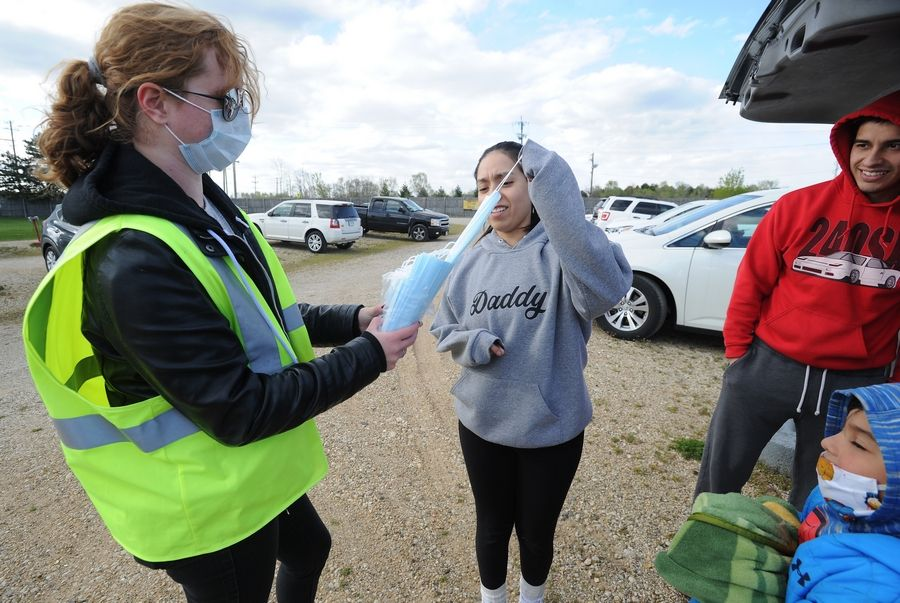 Kira Crippen, 19, of McHenry who works for the McHenry Outdoor Theater, hands out masks to taker Sofia Rodriguez, 27, of Woodstock who gets ready with her family to see the Flintstones and Jurassic Park at the outdoor drive-in.