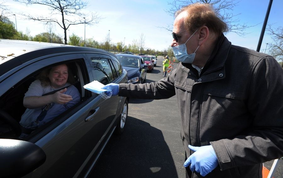 Schaumburg Mayor Tom Dailly hands out masks to Schaumburg resident Lisa Moore as she was one of hundreds who showed up at Boomers Stadium to collect their masks. 70,000 were to be passed out over the next three days if supplies lasted that long.