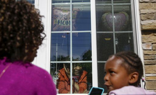 Mary Washington, 73, speaks through a window to her daughter, Courtney Crosby and grandchild Sydney Crosby for a Mother's Day celebration at Provident Village at Creekside senior living on Sunday, May 10, 2020, in Smyrna, Ga.