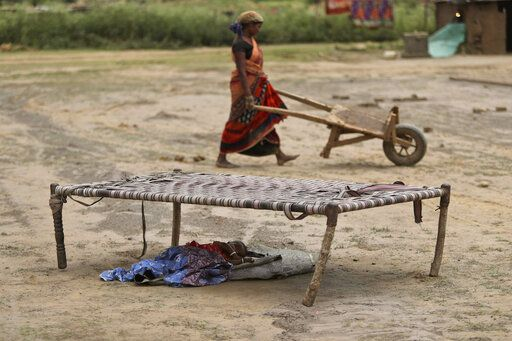 An Indian woman works at a brick kiln as her child sleeps under a cot during lockdown to curb the spread of new coronavirus on the outskirts of Jammu, India, Sunday, May 10, 2020. India's lockdown entered a sixth week on Sunday, though some restrictions have been eased for self-employed people unable to access government support to return to work.