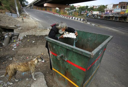 An Indian homeless man eats eggs discarded in a garbage bin during lockdown to curb the spread of new coronavirus on the outskirts of Jammu, India, Sunday, May 10, 2020. India's lockdown entered a sixth week on Sunday, though some restrictions have been eased for self-employed people unable to access government support to return to work.
