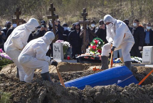 Grave diggers wearing protective suits bury a COVID-19 victim as relatives and friends stand at a safe distance, in the special purpose for coronavirus victims section of a cemetery in Kolpino, outside St.Petersburg, Russia, Sunday, May 10, 2020.