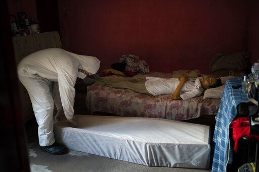 A worker of SOS Funeral, wearing protection equipment, prepares to remove the body of Eldon Cascais, who according to relatives, had pre-existing conditions and died at his house after having trouble breathing, amid the new coronavirus outbreak in Manaus, Brazil, Saturday, May 9, 2020.