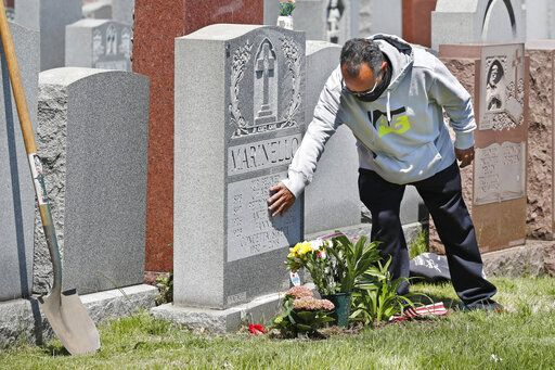 Anthony Garrita touches his great-aunt Concietta Sireci's gravestone at Calvary Cemetery on Mother's Day after planting flowers, Sunday, May 10, 2020, in New York. Garrita's grandparents and other relatives are also buried there. The cemetery had been closed due to concerns over the spread of coronavirus, but opened its gates for several hours Sunday to allow families to visit the gravesites of loved ones.