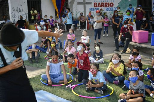 Children watch a performance by the National Circus Foundation of Venezuela at the San Juan neighborhood of Caracas, Venezuela, Saturday, May 9, 2020. The circus also does live stream performances at the National Caracas theater during the lockdown to prevent the the spread of the new coronavirus .