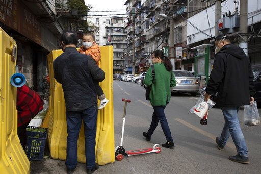 In this photo taken Wednesday, April 1, 2020, residents walk past a sealed off neighborhood in Wuhan, central China's Hubei province. Authorities in Wuhan, the Chinese city where the coronavirus pandemic first broke out, have reportedly launched a plan to test everyone in the city of 11 million people in the next 10 days.