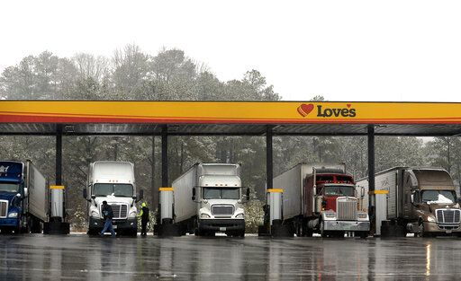 FILE - In this Feb. 11, 2014, file photo, truck drivers stop at a gas station in Emerson, Ga., north of metro Atlanta, to fill up their tractor trailer rigs. The Trump administration eased rules Thursday, May 14, 2020 that limit working hours for truck drivers, and the changes brought immediate protests from labor and safety groups. The Federal Motor Carrier Safety Administration extended the maximum working day for short-haul drivers from 12 hours to 14 hours and applied the longer hours to more drivers by expanding the geographic definition of short-haul driving.