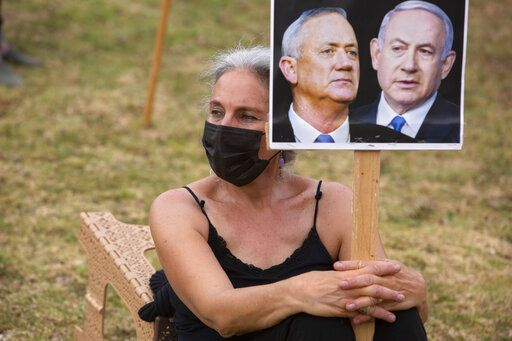 An Israeli woman holds a placard showing Israeli Prime Minister Benjamin Netanyahu and Blue and White party leader Benny Gantz, during a demonstration outside the Knesset, Israel's parliament in Jerusalem, Thursday, May 14, 2020. Prime Minister Benjamin Netanyahu and his rival-turned-partner, Benny Gantz, on Thursday postponed the swearing-in of their controversial new government as the Israeli leader rushed to quell infighting within his Likud party.