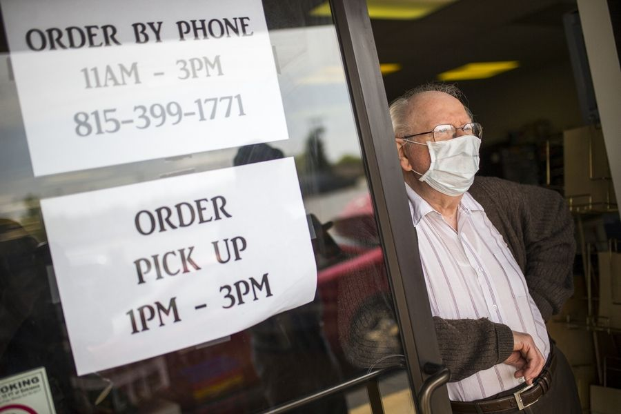 Kenneth Lythgoe, owner of Royal Hobby, who has had to adapt to the pandemic safety procedures with new curbside pick-up, stands in the doorway of his store, Saturday, in Rockford. More than 2,000 additional cases of the coronavirus have been confirmed in Illinois and 74 more people have died, health officials said Saturday.