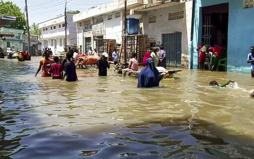 In this image made from video taken Sunday, May 17, 2020, people wade through a flooded street in Beledweyne, central Somalia. Flooding in central Somalia has affected nearly 1 million people, displacing about 400,000, the United Nations said Monday, May 18, 2020 warning of possible disease outbreaks because of crowding where the displaced are seeking temporary shelter.