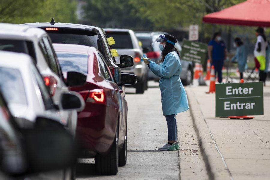 A worker instructs people on how to collect their own nasopharyngeal swab samples to test for the coronavirus at a drive-thru testing site organized by the nonprofit organization Community Organized Relief Effort at Dr. Jorge Prieto Math and Science Academy in Chicago on Monday.