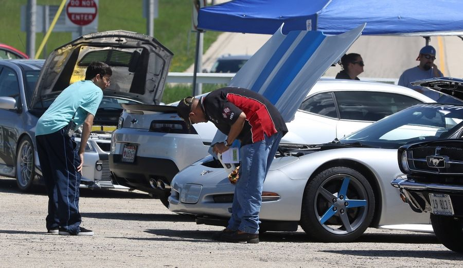 A spectator watches Rick Escevedo of Chicago polish his 2003 convertible Chevy Corvette during the 2018 Lambs Farm Champion Car Show. The juried show featured a wide variety of makes and models of cars.