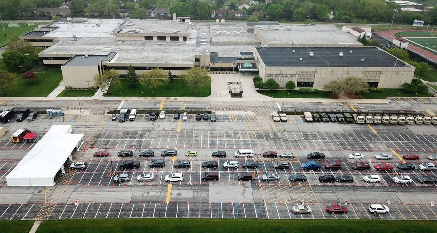 This is an aerial view of vehicles lined up for COVID-19 tests at the state's new drive-through center at Rolling Meadows High School Friday. The test is self-administered; test kits are passed through a partially opened car window.