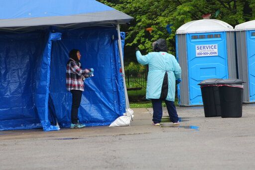 In this May 14, 2020 photo, a woman gets tested at a new testing site in the Little Village neighborhood of Chicago. Chicago's Little Village neighborhood is known as the heart of Mexican culture in the city. It's also located in the zip code area with one of the highest rates of positive coronavirus cases in the city. Across the country, states reporting racial data indicate similar trends, with overwhelmingly high rates of infection within the Latino population.