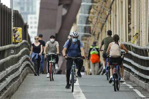 Cyclists and pedestrians move along the Queensboro Bridge, Friday, May 22, 2020, in New York.