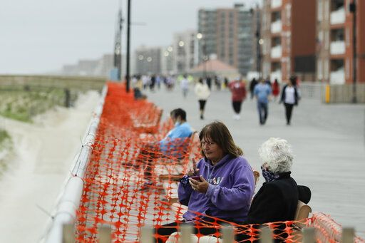 People engage in social distancing on the boardwalk during the coronavirus pandemic Friday, May 22, 2020, in Long Beach, N.Y.