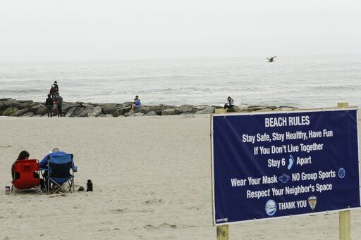 People engage in social distancing on the beach during the coronavirus pandemic, Friday, May 22, 2020, in Long Beach, N.Y.