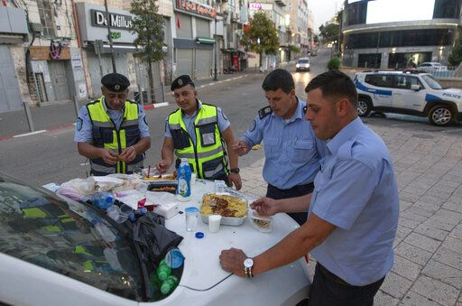 In this Tuesday, May 19, 2020, photo, Palestinian policemen have their Iftar breaking a Ramadan fasting day at the street while the state of emergency continues, overlooking the lockdown and quarantine measures to protect residents from the coronavirus, in the West Bank city of Ramallah. Muslims worldwide will celebrate one of their biggest holidays under the long shadow of the coronavirus. The three-day Eid al-Fitr, expected to begin Saturday or Sunday, marks the end of the fasting month of Ramadan for the world's 1.8 billion Muslims.