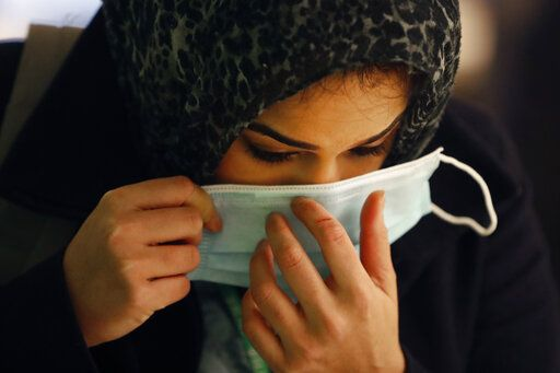FILE - In this April 22, 2020, file photo, RUSH Hospital respiratory therapist Jumana Azam puts on a surgical mask after standing before a face temperature scanner as she reports for her early morning shift at the hospital in Chicago. Muslims worldwide will celebrate one of their biggest holidays under the long shadow of the coronavirus. The three-day Eid al-Fitr, expected to begin Saturday or Sunday, marks the end of the fasting month of Ramadan for the world's 1.8 billion Muslims.
