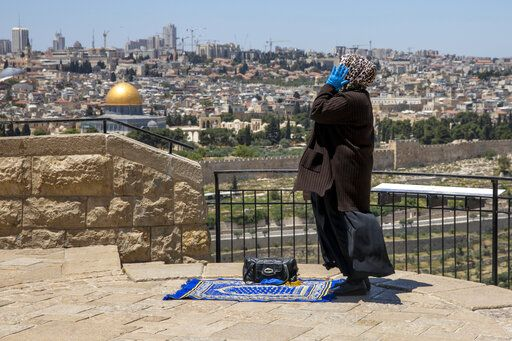 FILE - In this May 1, 2020, file photo, a Muslim woman wears gloves prays in east Jerusalem's Mount of Olives, overlooking the Dome of the Rock and al-Aqsa mosque compound, which remains shut to prevent the spread of coronavirus during the holy month of Ramadan. Muslims worldwide will celebrate one of their biggest holidays under the long shadow of the coronavirus. The three-day Eid al-Fitr, expected to begin Saturday or Sunday, marks the end of the fasting month of Ramadan for the world's 1.8 billion Muslims.