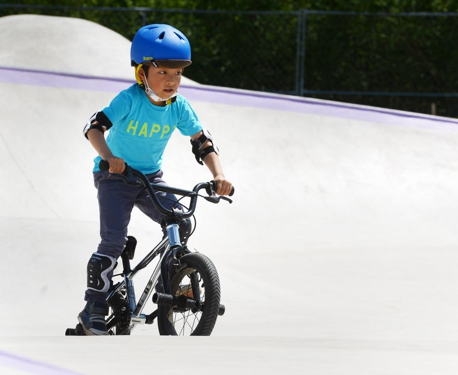 Yuki Oi, 5, rides his bike during the opening weekend of the Vernon Hills Park District's new skate park near the Sullivan Community Center Saturday.