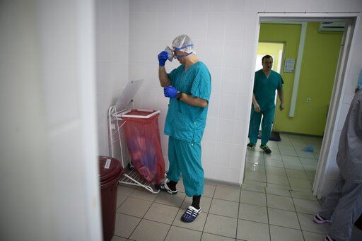 In this photo taken on Friday, May 15, 2020, Dr. Osman Osmanov takes off a mask after his shift at an intensive care unit of the Filatov City Clinical Hospital in Moscow, Russia. Moscow accounts for about half of all of Russia's coronavirus cases, a deluge that strains the city's hospitals and has forced Osmanov to to work every day for the past two months, sometimes for 24 hours in a row.