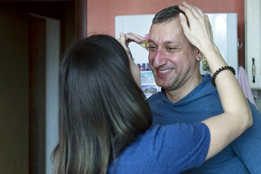In this photo taken on Saturday, May 16, 2020, Dr. Osman Osmanov is greeted by his wife Saida after a shift at an intensive care unit of Filatov City Clinical Hospital in Moscow, Russia. Moscow accounts for about half of all of Russia's coronavirus cases, a deluge that strains the city's hospitals and has forced Osmanov to to work every day for the past two months, sometimes for 24 hours in a row.