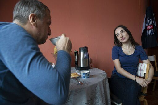 In this photo taken on Saturday, May 16, 2020, Dr. Osman Osmanov drinks coffee with his wife Saida at home after his shift at an intensive care unit of Filatov City Clinical Hospital in Moscow, Russia. Moscow accounts for about half of all of Russia's coronavirus cases, a deluge that strains the city's hospitals and has forced Osmanov to to work every day for the past two months, sometimes for 24 hours in a row.