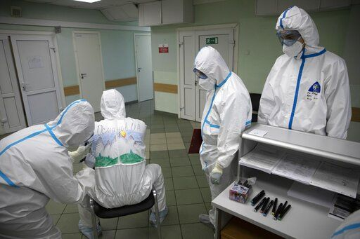 In this photo taken on Saturday, May 16, 2020, Dr. Osman Osmanov waits as a medical worker paints his protective gear during a rest on his shift at the Filatov City Clinical Hospital in Moscow, Russia. Moscow accounts for about half of all of Russia's coronavirus cases, a deluge that strains the city's hospitals and has forced Osmanov to to work every day for the past two months, sometimes for 24 hours in a row.