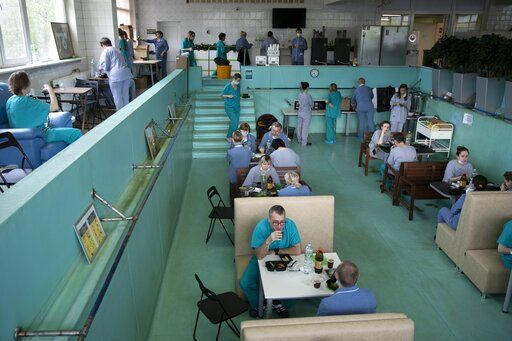 In this photo taken on Friday, May 15, 2020, Dr. Osman Osmanov, center, has breakfast before his shift at an intensive care unit of the Filatov City Clinical Hospital in Moscow, Russia. Moscow accounts for about half of all of Russia's coronavirus cases, a deluge that strains the city's hospitals and has forced Osmanov to to work every day for the past two months, sometimes for 24 hours in a row.