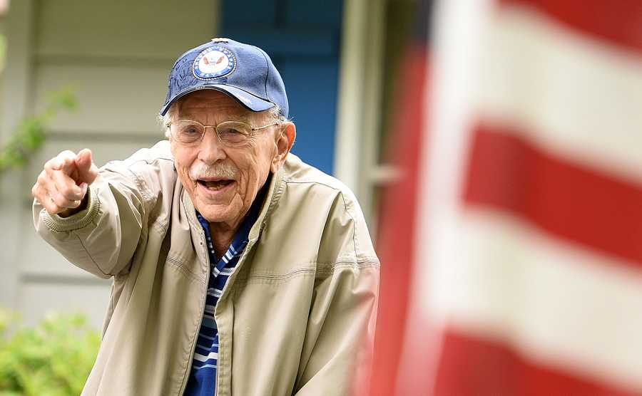 Naperville resident and World War II veteran Bob Piper points back at someone yelling out congratulations to him during a drive-by parade celebrating his 98th birthday Friday.