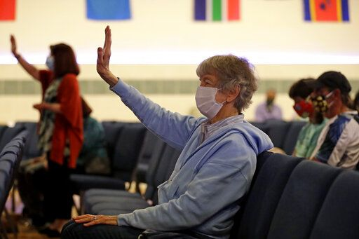 Anita Edwards, center and Lakewood Chapel Church members pray during a Memorial Day service in Arlington Heights, Ill., Sunday, May 24, 2020, while wearing masks and observing social distancing during the coronavirus pandemic.