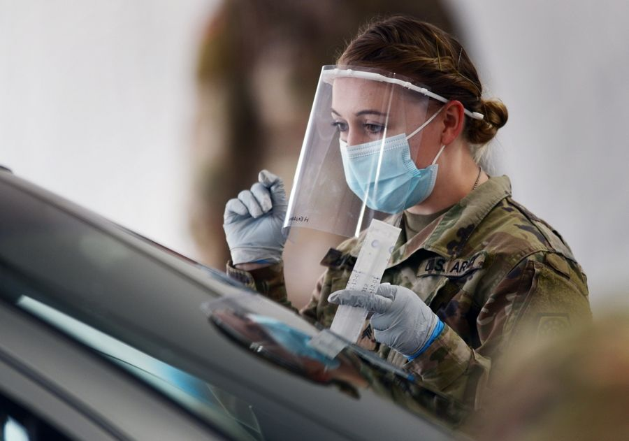 Members of the Illinois National Guard work with the public at the state's new drive-through COVID-19 testing facility at Rolling Meadows High School Friday. The test is self-administered by the person being tested, and the test kits are passed through the partially-opened car window.